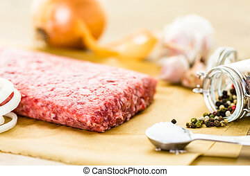 Ground pork on the table with other ingredients for recipe.