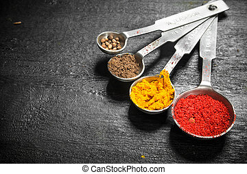 Ground spices in measuring spoons.