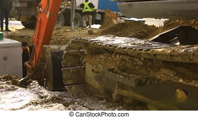 Close up processes during the early stage of a construction site, details of a continuous track of excavator with blurry tradesmen working in background