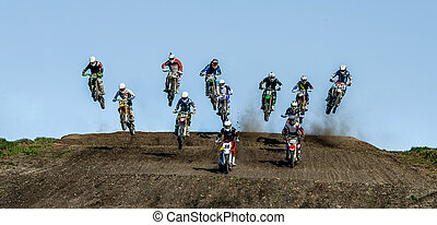 group athletes motocross riders coming off jump