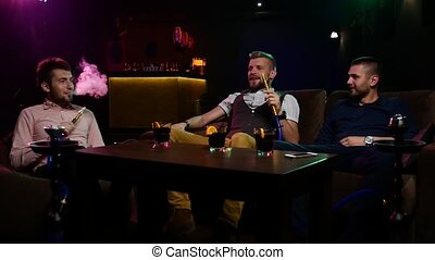 Group Boys smoking hookah in the lounge caffee. Slow motion