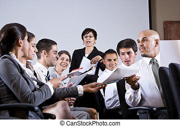 Group business presentation handing out papers - Hispanic...