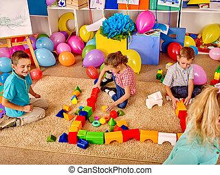 Group children game blocks on carpet floor .