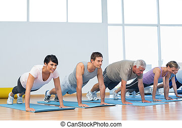 Group doing push ups in row at yoga class - Fitness group ...