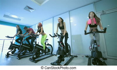 Five sports friends pedaling - Group exercises in the gym. ...