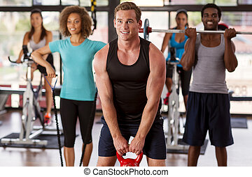 Group exercising in a gym - Multi-ethnic gym class doing...