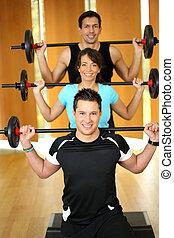 Group having fun with weightlifting - People enjoying ...