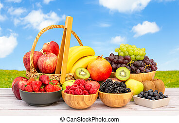 Group Healthy fresh fruit in a wooden basket, With vitamins c from bananas, kiwi, grapes, raspberries, blueberries, and blackberries, good for the body and diet food on the table in nature background.