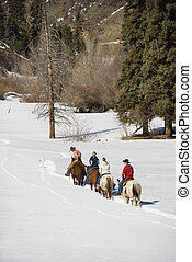 Group horseback riding in snow. - Small group of people...