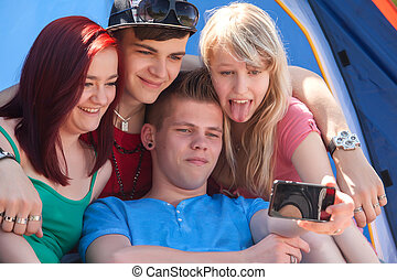 group is taking a photo while girl sticks her tongue out -...
