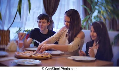 group kids family of people eat pizza at a cafe. close-up children teens eating fast food in cafe slow motion video indoors