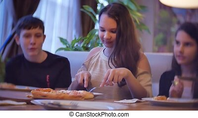 group kids family of people eat pizza at a cafe. close-up children teens eating indoors fast food in cafe slow motion video