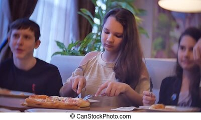 group kids family of people eat pizza at a cafe. close-up children teens indoors eating fast food in cafe slow motion video