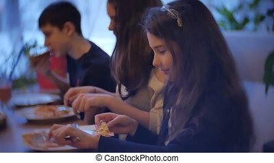 group kids family of people eat pizza at a cafe. close-up indoors children teens eating fast food in cafe slow motion video