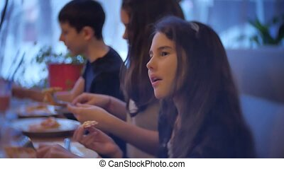 group kids family of people eat pizza at a cafe. indoors close-up children teens eating fast food in cafe slow motion video