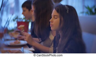 group kids family of people eat pizza at a cafe indoors. close-up children teens eating fast food in cafe slow motion video