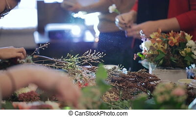 Group master florists, working with flowers, bouquets, boutonnieres, herbs, plants, decorations