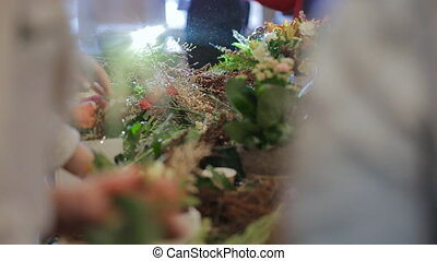 Group master florists, working with flowers, bouquets, boutonnieres, herbs, plants