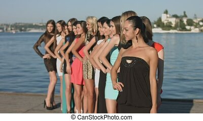 Group models in dresses standing in the row near the sea