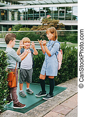 Group of 3 kids playing Rock, Paper, Scissors game on schoolyard. Back to school concept, fashion for children