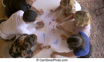 Group of 5 women and a man discussing successful profits with charts and graphs