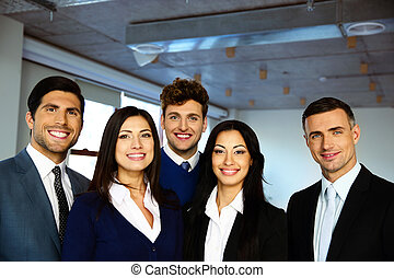 Group of a happy business people standing together in office