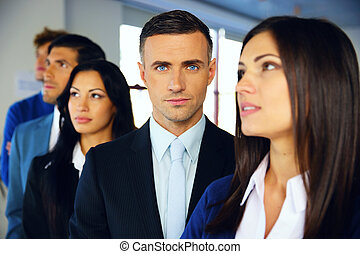 Group of a young serious businesspeople standing in row at office