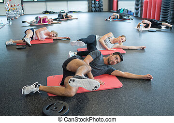 group of adults doing exercises in gym