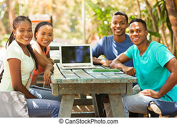 group of african college friends sitting outdoors