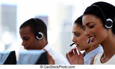 Group of agents in a call centre smiling and helping people