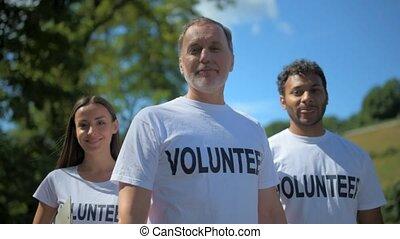 Group of amiling international volunteers tanding in the...