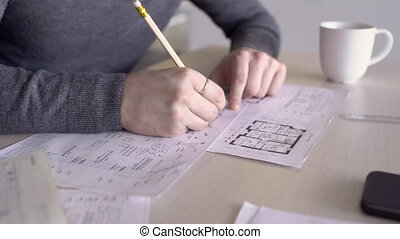 Group of architects at desk works with drawings on notes in the diary.