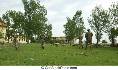 Group of army soldiers patrolling in abandoned housing area...