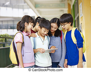 group of asian pupils using tablet computer at school