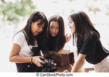 group of asian teenager holding camera and acoustic guitar ...