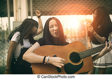group of asian teenager standing outdoor plying spanish...