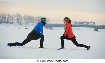 Group of athletes doing the exercise in winter field