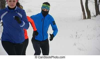 Group of athletes jogging in winter forest, sport and...