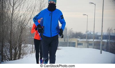 Group of athletes jogging in winter forest