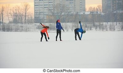 Group of athletes warming up and stretching before exercise in winter forest