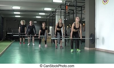 Group of athletic people synchronously do deadlift in a gym...