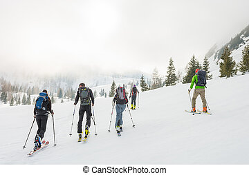 Group of back country skiers walking through a misty valley.