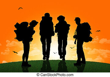 silhouettes of a group of backpackers, men and a women, walking together on a top of the hill towards the sunset and waiting for their friends
