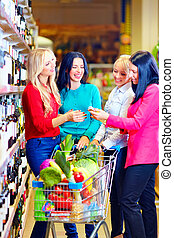 group of beautiful girls choosing wine in supermarket