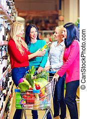 group of beautiful girls choosing wine in supermarket