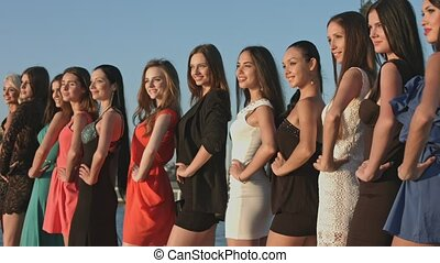 Group of beautiful girls in dresses and heels posing while standing in the row