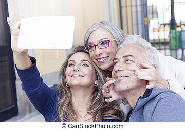group of beautiful mature people taking a selfie waiting for the train