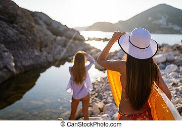 Group of beautiful young women friends walking on the beach