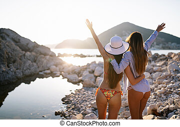 Group of beautiful young women friends walking on the beach