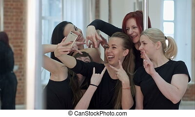 Group of beautiful young women taking a selfie after a pole dance class